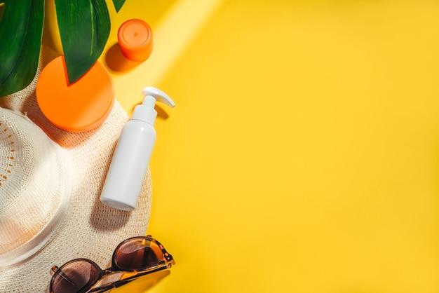 Zonnescherm. vrouw hoed met zonnebril en bescherming crème spf flat lag op gele achtergrond. strandaccessoires. zomer reizen vakantie concept