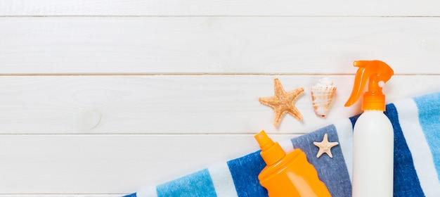 Zonneschermflessen met zeester en blauwe handdoek op witte houten lijstbanner met exemplaarruimte. reizen gezondheidszorg accessoires bovenaanzicht