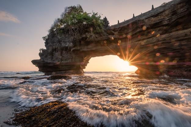 Zonneschijn door van rotsachtige klip op kust bij zonsondergang