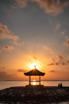Zonneschijn over paviljoen op pier bij kustlijn in ochtend