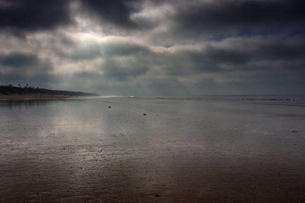 Zonnestralen breken door stormwolken op de stranden van cadiz