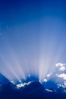 Zonnestralen oprijzen uit een grote wolk in intens blauwe lucht op een zomerse middag