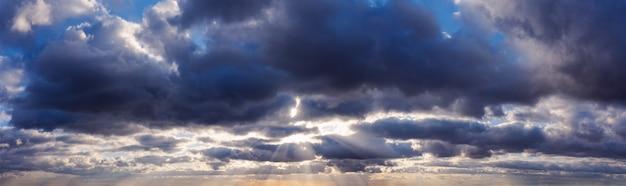 Zonnestralen schijnen door donkere regenachtige wolken aan de hemel.