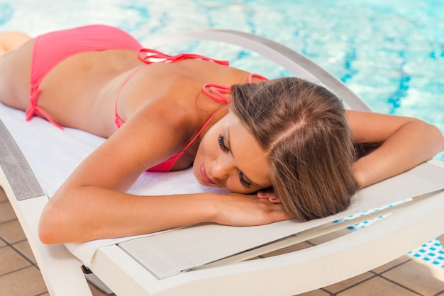 Zonnestralen vangen bij het zwembad. mooie jonge vrouw in bikini die op een ligstoel bij het zwembad ligt en de ogen gesloten houdt