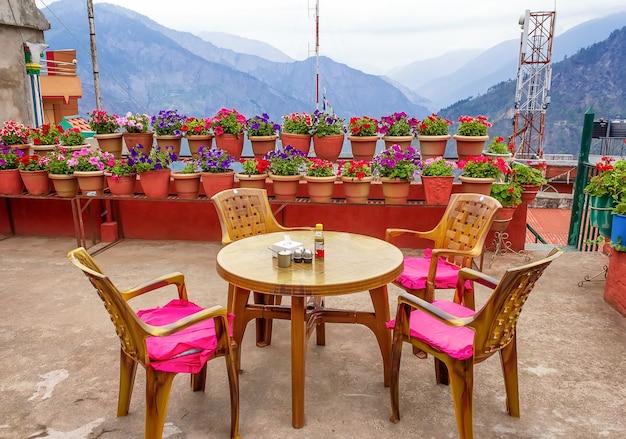 Zonneterras met tafel, stoelen en bloempotten. berg uitzicht. nepal