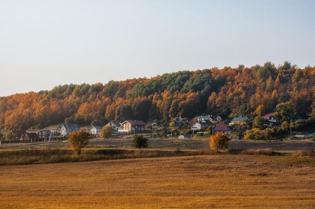 Zonnig avondlandschap met beplant landbouwgrond, met een dorp op een heuvel