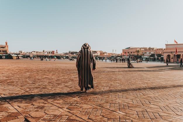 Zonnig landschap van een arabisch mannetje in gestripte thawb die in het grote stedelijke gebied loopt