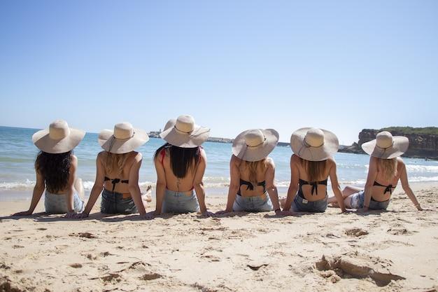 Zonnig landschap van jonge vrouwtjes in bikini's die op het strand poseren