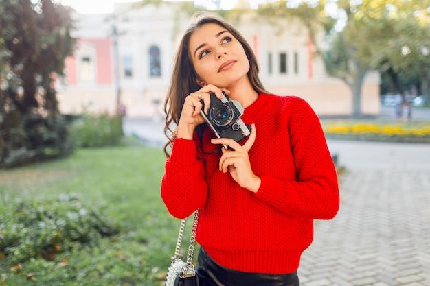 Zonnig levensstijlbeeld van vrij donkerbruin meisje in rode toevallige trui en rok die foto's maken door fotocamera in zonnig park. wandelen in de stadstuin en op zoek naar bezienswaardigheden.