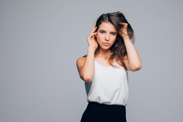 Zonnig meisje in mode moderne jurk is poseren in studio op witte achtergrond