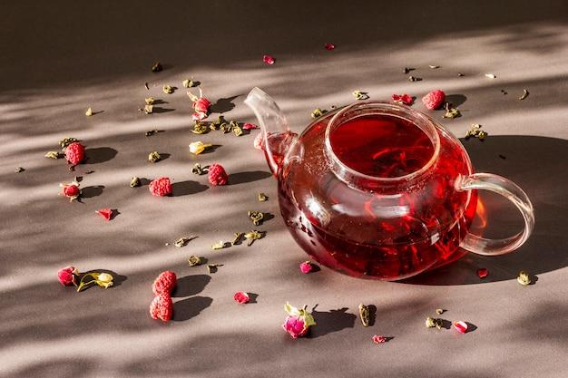 Zonnig ochtendontbijt. zoete framboos groene thee in glazen waterkoker met droge vruchten, bloemen en bladeren