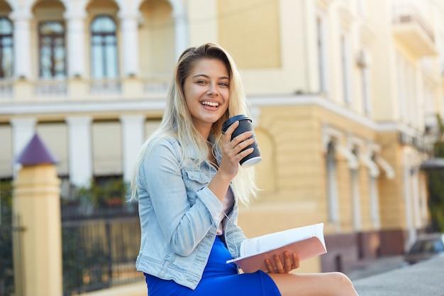 Zonnig openluchtportret van leuke blonde jonge vrouw met neer haar kleedde een denimjasje en blauwe rok