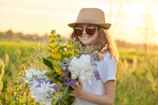 Zonnig openluchtportret van meisjeskind 9, 10 jaar oud in hoedzonnebril met boeket van bloemen in weide