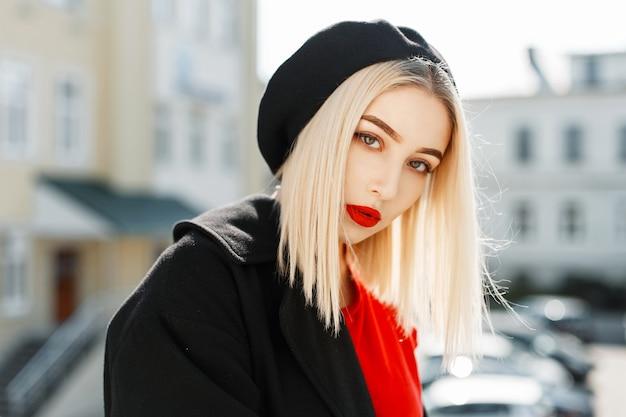Zonnig portret van een mooie jonge vrouw met rode lippen in trendy herfstkleren op straat