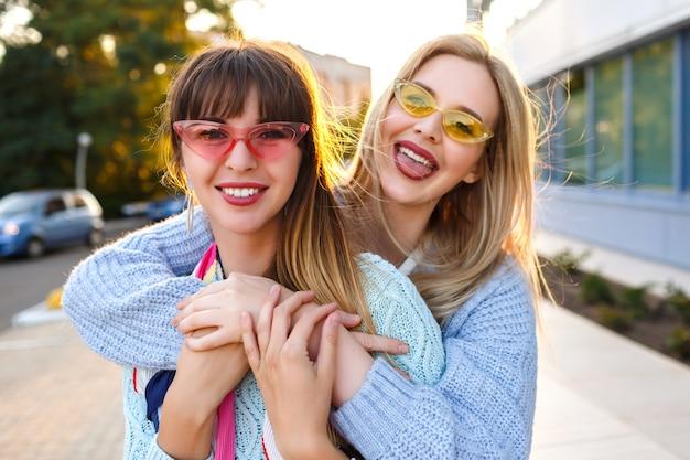 Zonnig positief portret van gelukkig lesbisch koppel genieten van tijd samen, zonnige kleuren, trendy pastel outfits en zonnebrillen, lente herfst tijd, prettige vakantie in europa.