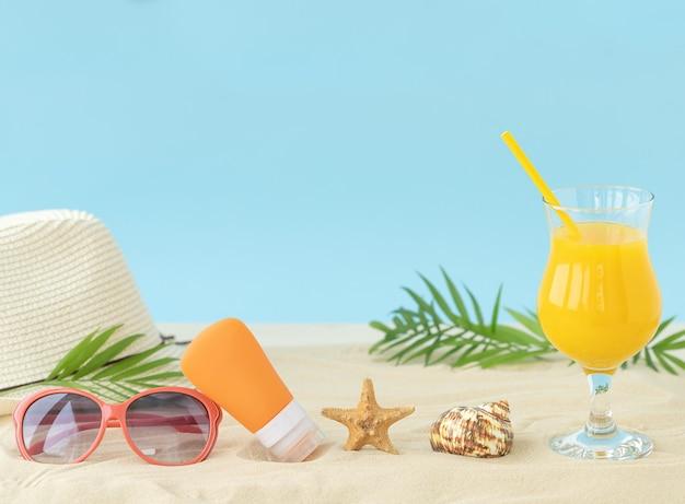 Zonnig strand met zomeraccessoires, glas sinaasappelsap, hoed, zonnebril, zonnebrandcrème en zeesterren