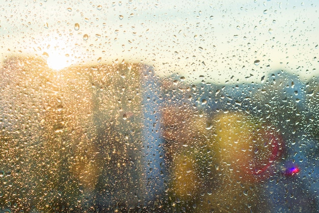 Zonnig venster als achtergrond met glanzende regendalingen