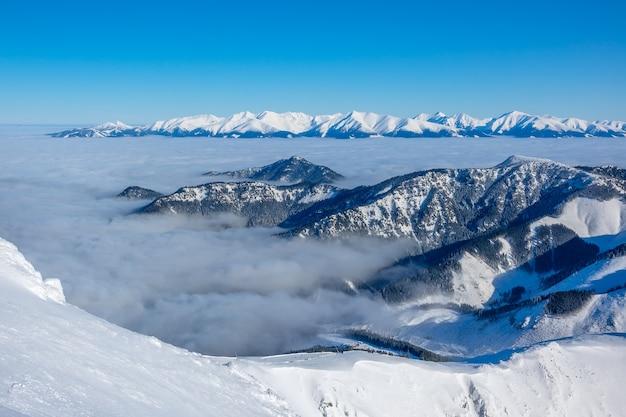 Zonnig weer en blauwe lucht. de toppen van winterbergen en lichte mist in de valleien