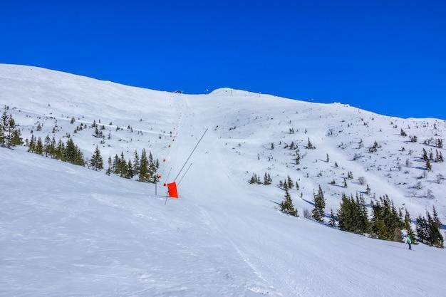 Zonnig weer in het skigebied. blauwe lucht. lange rechte skipiste met sneeuwkanonnen