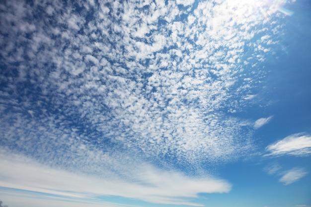 Zonnige achtergrond, blauwe lucht met witte wolken, natuurlijke achtergrond.