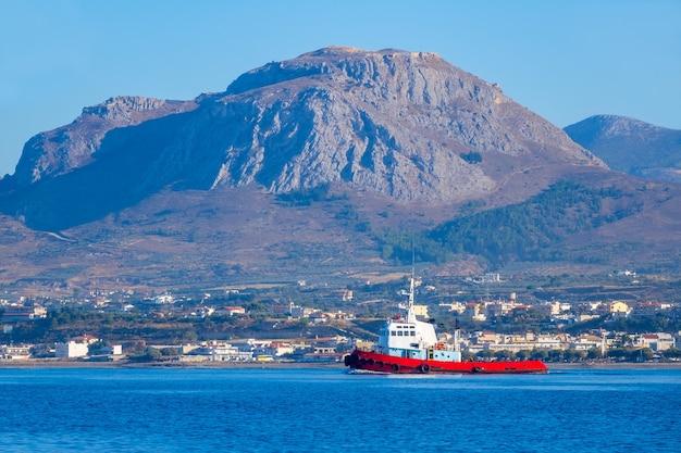 Zonnige bergachtige kust en sleepboot