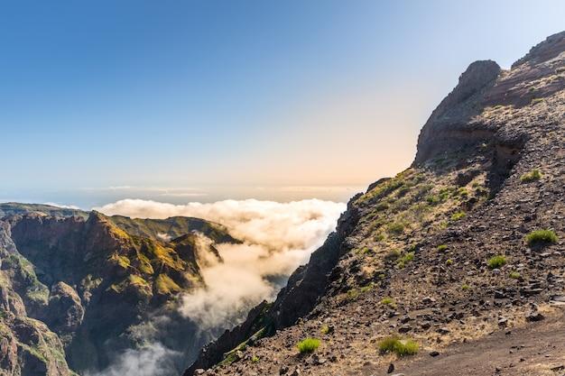 Zonnige bergen in wolken
