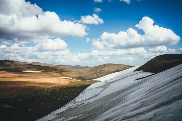 Zonnige bergwoestijnreliëf met lange gletsjer op helling in zonlicht onder blauwe bewolkte hemel. schilderachtig hooglandlandschap met lange kleine gletsjer op de berghelling en smeltwaterstromen hoog in de bergen.