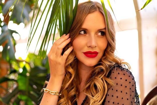Zonnige close-up portret van mooie jonge krullende vrouw poseren in de buurt van tropische bladeren wintertuin, avond glamour outfit en make-up.