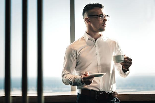 Zonnige dag. knappe zakenman permanent in de buurt van het raam genieten van zonnige dag en koffie drinken