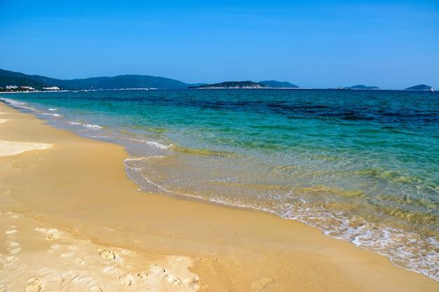 Zonnige dag, krakend zand, heldere turquoise zee, koraalriffen aan de kust van yalong bay in de zuid-chinese zee. sanya, eiland hainan, china. natuur landschap.