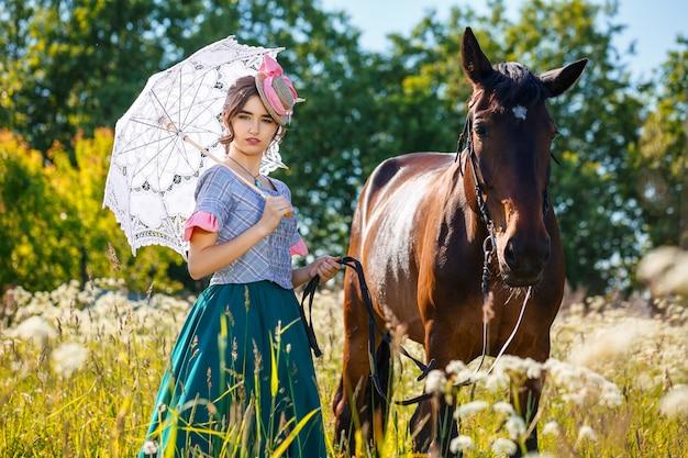 Zonnige dag mooie vrouw die zich naast het paard bevindt