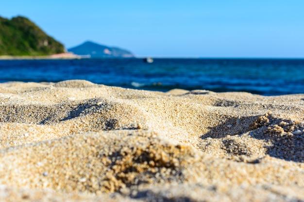 Zonnige dag, zand, heldere turquoise zee, koraalriffen aan de kust van xiaodonghai bay in de zuid-chinese zee. sanya, eiland hainan, china. natuur landschap.