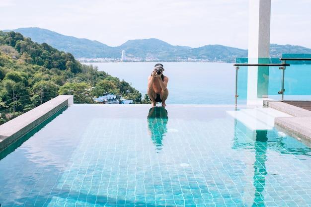 Zonnige foto van een poseren fotograaf zittend op de rand van het zwembad met een camera in zijn handen
