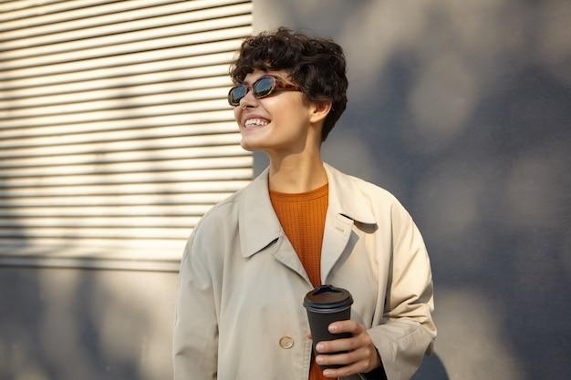 Zonnige foto van mooie jonge brunette gekrulde vrouw met casual kapsel zwart papier beker in opgeheven hand houden en vrolijk opzij kijken met een brede glimlach, gekleed in trendy outfit