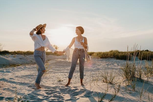 Zonnige gelukkige twee jonge vrouwen die plezier hebben op het zonsondergangstrand, homo-lesbische liefde romantiek