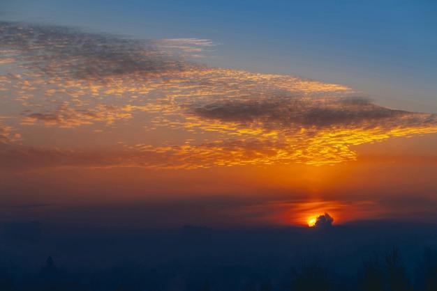 Zonnige glans op wolken. prachtige levendige dageraad. mooie rustige oranje zonsondergang. schilderachtige surrealistische zonsopgang