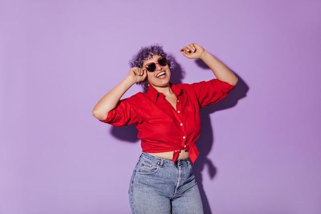 Zonnige heldere vrouw in rood shirt met lange mouwen vastgebonden in de taille. kortharige vrouw met lila haar in jeans en glazen glimlachen.