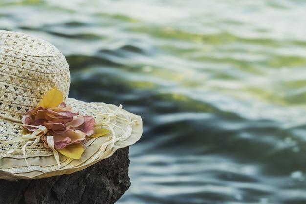Zonnige hoed met bloemen ligt op een rots in de buurt van de zee, afgezwakt