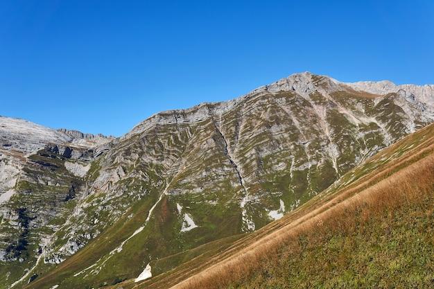 Zonnige hooglandhellingen met herfstalpenweiden en stroken van geologische lagen - uitlopers van mount fisht in de kaukasus