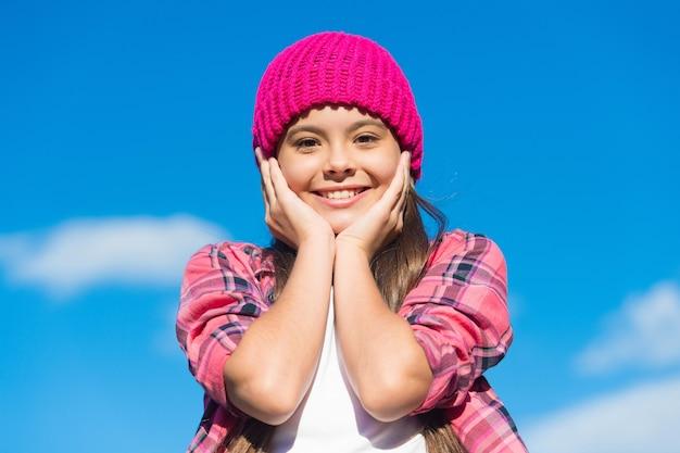 Zonnige huidverzorging. gelukkig meisje aanraking gezicht huid op blauwe hemel. schoonheid blik van klein kind. zomerse huidverzorgingsroutine. cosmetica voor babyhuidverzorging. schoonheid en verzorging. natuurlijke huidverzorgingsproducten speciaal voor jou gemaakt.