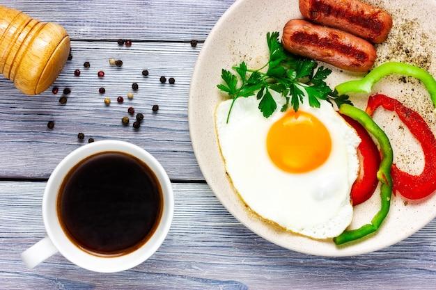 Zonnige kant naar boven gebakken eieren met worstgroenten en kopje koffie op een licht houten tafelblad
