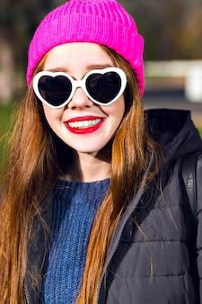 Zonnige lente portret van gelukkig vrolijk lachende gember vrouw poseren in het park, geniet van zonnige dag, heldere punk hipster hoed, hartige zonnebril, rode lippen, warme parka, positieve stemming.