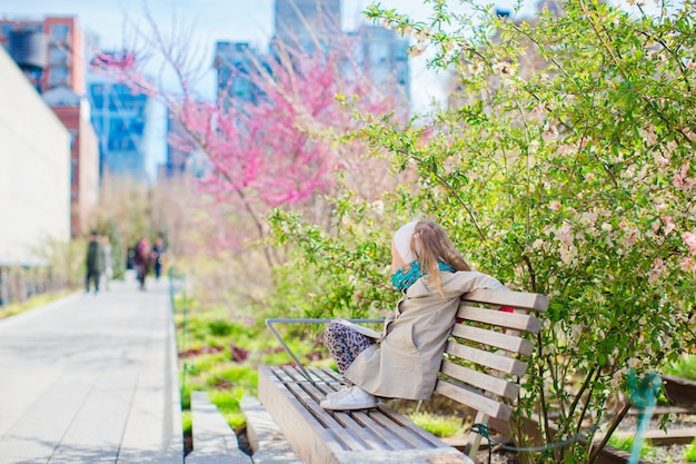 Zonnige lentedag op de high line van new york. het meisje geniet in openlucht van de vroege lente in de stad