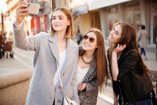 Zonnige levensstijlbeeld van beste vriendenmeisjes die selfie op smartphone nemen