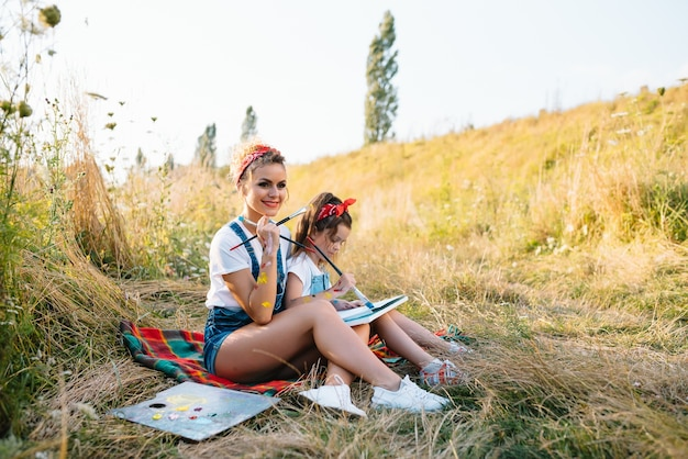 Zonnige natuur, moeder en dochter schilderen een foto in een park, schilderen een klein kind, kindercreativiteit.