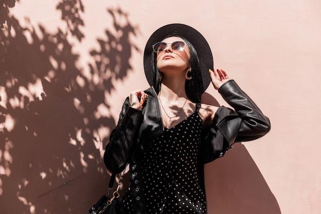 Zonnige portret mooie jonge brunette vrouw in elegante hoed in mooie jurk in modieuze zonnebril in lederen zwarte jas met jurk in de buurt van roze muur op strand. sexy meisje in trendy outfit