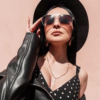 Zonnige portret mooie jonge brunette vrouw in elegante hoed in mooie jurk in modieuze zonnebril in lederen zwarte jas met jurk in de buurt van roze muur op strand. sexy meisje in trendy zomeroutfit.