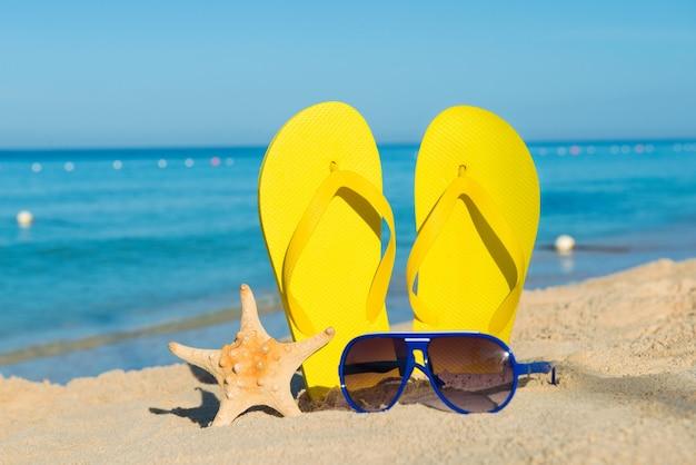 Zonnige positieve strandvakantie. gele sandalen, zonnebrillen en zeesterren op een achtergrond van de zee