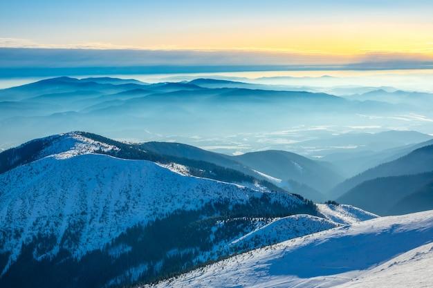 Zonnige winterdag op de top van de berg. veel bergtoppen omgeven door lichte mist