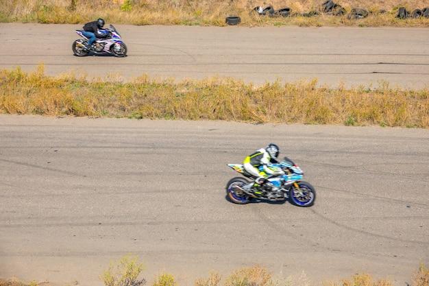 Zonnige zomerdag. een recht stuk van de oude snelweg. twee motorrijders strijden in snelheid op sportfietsen
